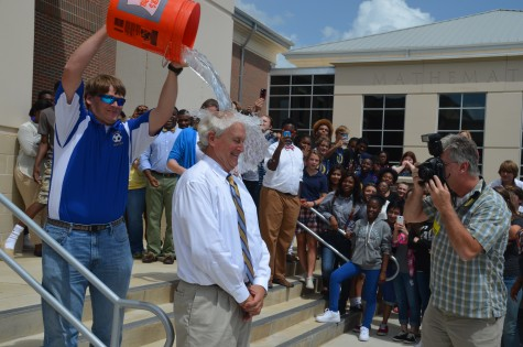 SLOW TO REACT: Principal Mike Martin is splashed with water by ELL teacher Thomas Herrington as the school watches on.