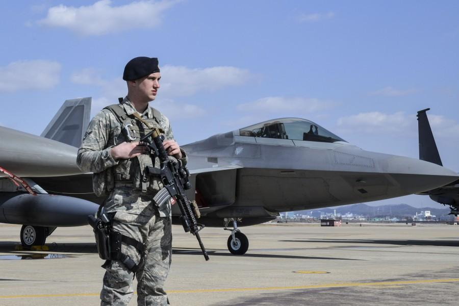 An Air Force Security Forces member stands guard next to an F22 Raptor fighter aircraft from Kadena Air Base, Japan, after it conducted a flyover in the vicinity of Osan Air Base, South Korea, in response to recent provocative action by North Korea, Feb. 17, 2016. It was joined by three other Raptors, four F-15 Slam Eagles and four U.S. Air Force F-16 Fighting Falcons. The F-22 is designed to project air dominance rapidly and at great distances and currently cannot be matched by any known or projected fighter aircraft. (U.S. Air Force photo by Tech. Sgt. Travis Edwards/Released)