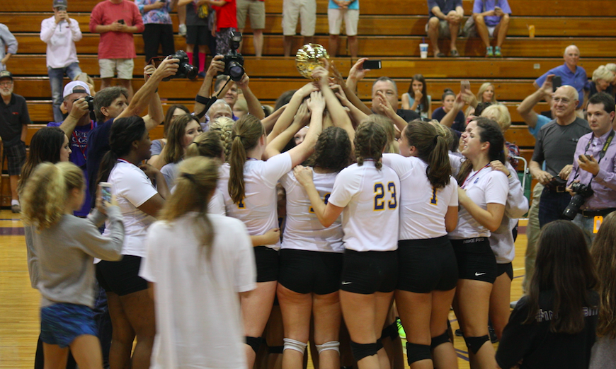 The OHS volleyball team hoists the golden ball after winning the MHSAA Class II State Championship.
