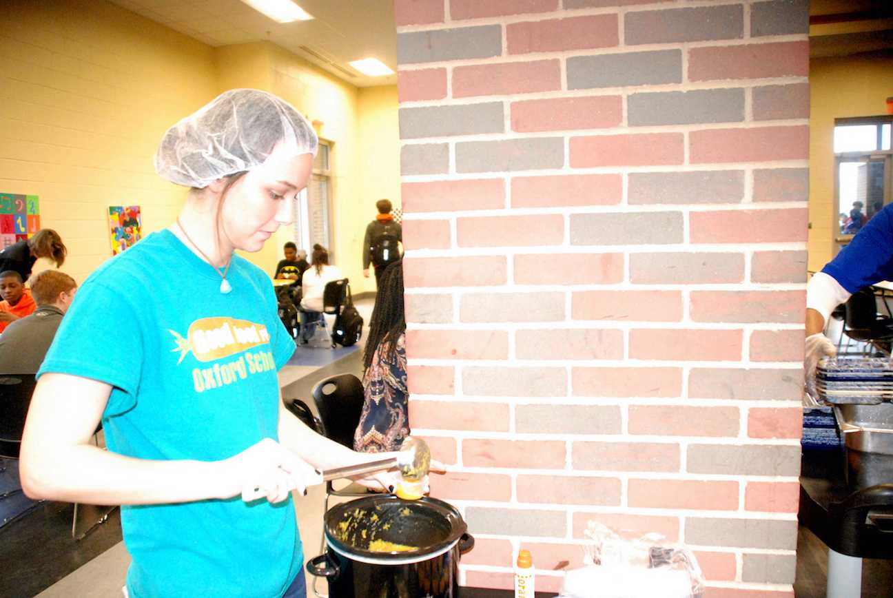 A member of Good Food for Oxford Schools fills a cup with a sample of butternut squash soup to serve to students during lunch.