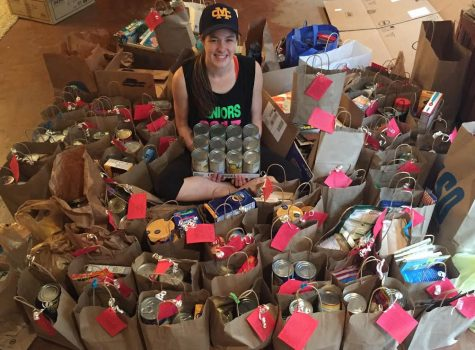 Senior Swayze Elliott sits among cans that she collected for a neighborhood food pantry drive.