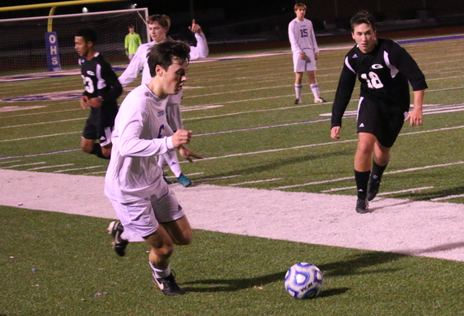 Senior forward Neil Chandler dribbles the ball upfield.