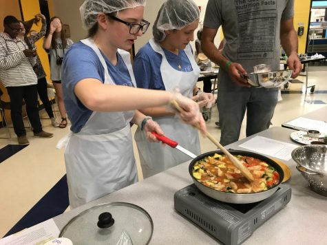 Junior Emily Hollowell (left) and sophomore Justine Perrier (right) of the Delicious Duo team cook their meal of choice for the Iron Chef competition on April 30.