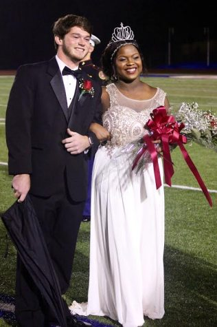 Senior Samya Clayton getting escorted by her date after being crowned homecoming queen last October.