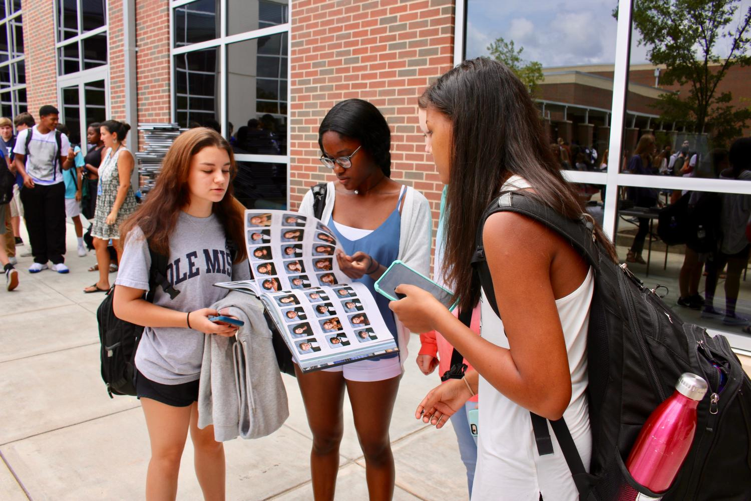 Juniors Shannan Ray, Tamara Mayes, and Syrena Sisk look through pictures in their yearbook at the signing party.