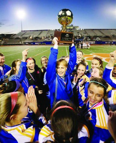 Girl's head soccer coach Hunter Crane hoists the state championship trophy.