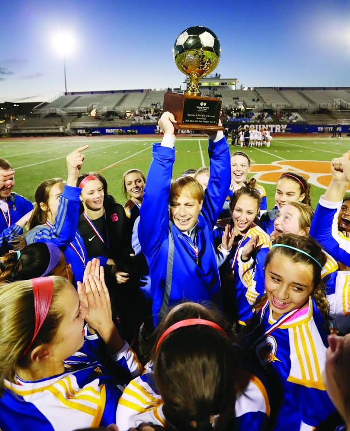 Girl%27s+head+soccer+coach+Hunter+Crane+hoists+the+state+championship+trophy.