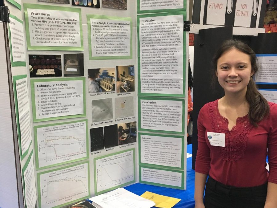 Junior+Siena+Cizdziel+stands+in+front+of+her+award-winning+science+fair+project.+For+the+project%2C+she+studied+the+effects+that+small+pieces+of+plastic+can+have+on+the+ecosystem.