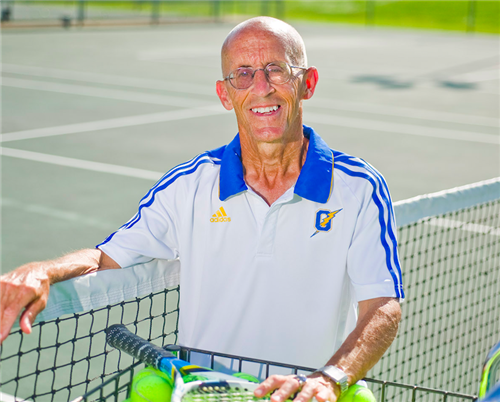 Tennis coach Louis Nash smiles on the tennis court. Nash has been coaching at Oxford nineteen years.