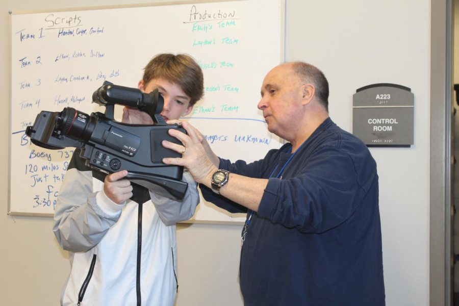 Broadcast Journalism teacher Keith Scruggs helps freshman Joel David Montgomery with one of the broadcast cameras. Scruggs has taught for six years, but this is his first year teaching at OHS.