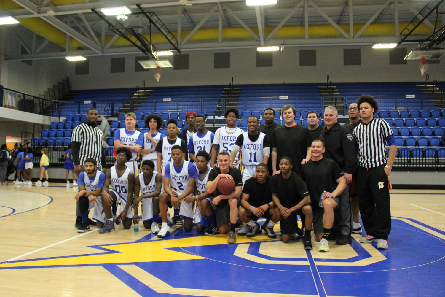 Unified Sports basketball team, Oxford Police Department officers, and the Unified Sports' referees stand and smile after their game. The game resulted in a tie with a score of 40-40 after game tying threes were scored in the final seconds.
