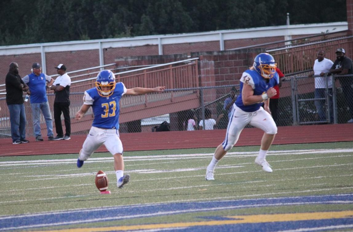 Junior Jack Tannehill kicks the ball off as senior Clay Cromwell runs to cover the kick against Charleston.  Cromwell scored the first touchdown of the 21-6 Charger win last Friday night.