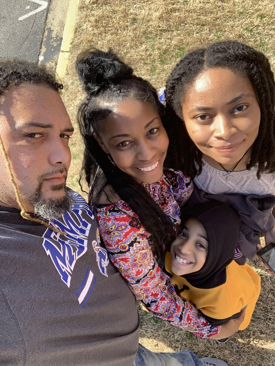 Art teacher Kevin Jones stands and smiles with his family in a selfie. Jones moved to Oxford this year in order to become the new art teacher.