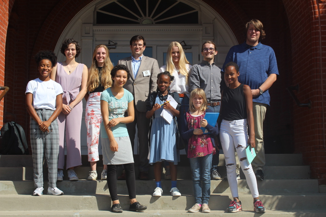 Seniors Cooper Crawley, Amya Franklin, Lily Hemmins, Patricia Hughes, Donald Rogers, and Sophie Quinn and four young girls stand and smile at the courthouse. They participated in a meeting with a representative for Mississippi Representative Trent Kelly concerning climate change.