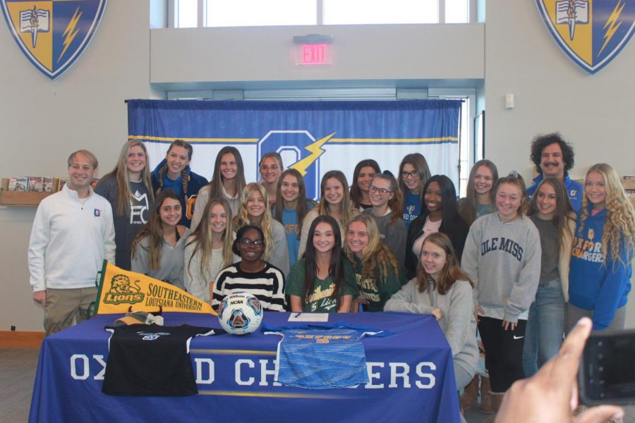 Members of the OHS Girls' Soccer Team smile and stand around seniors Maria Jones and Kathleen Myers. Jones and Myers both participated in College Signing Day on Nov. 13.